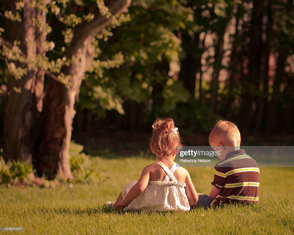Boy and girl twins sitting on the grass : Stock Photo