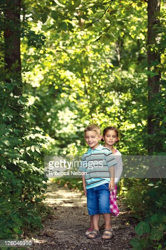 Boy and girl twins standing on forest path : Stock Photo