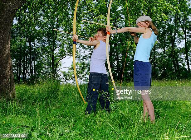 Boy and girl (8-11) using bow and arrow, outdoors