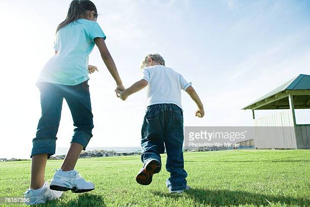 Boy and girl walking across grass