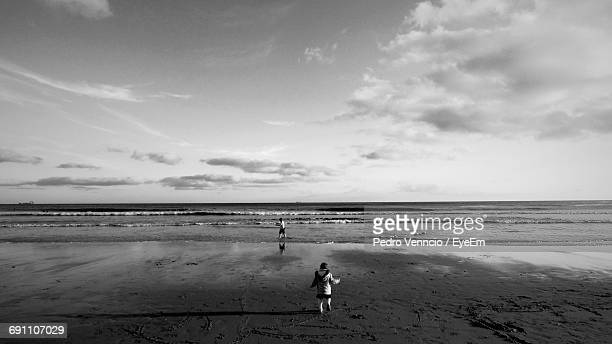 Boy And Girl Walking At Beach Against Cloudy Sky
