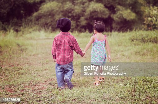 Boy and girl walking hand in hand : Stock Photo