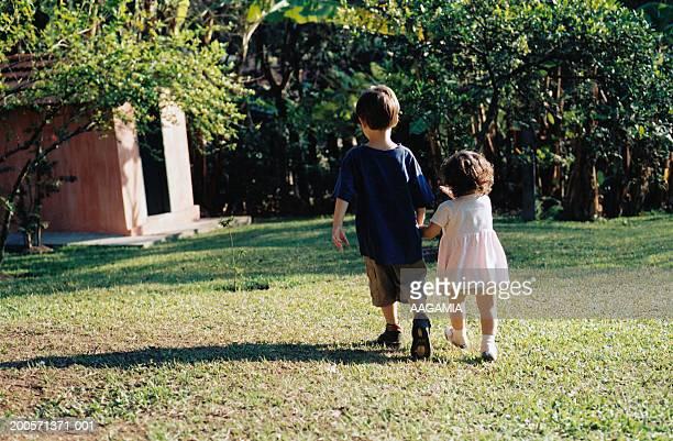 Boy and girl (3-5) walking in garden, rear view