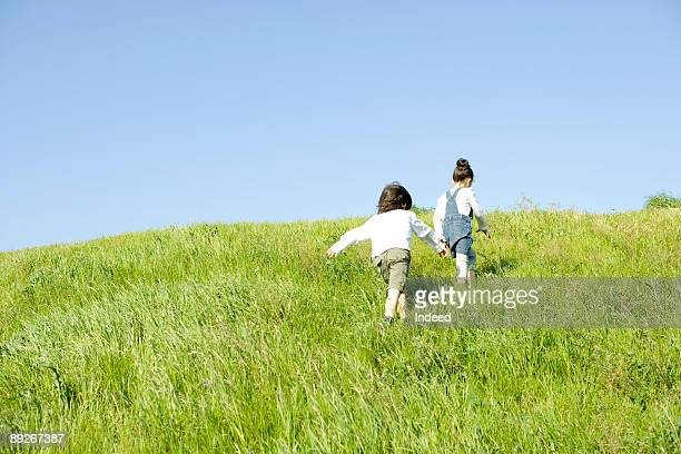 Boy and girl (6-9) walking on grass, rear view