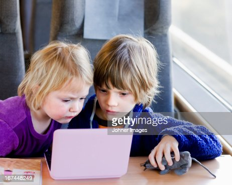 Boy and girl watching film in train : Stock Photo