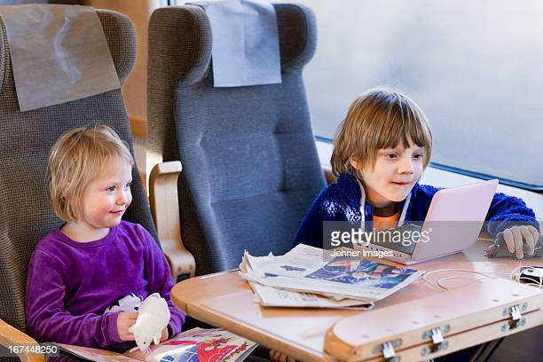 Boy and girl watching film in train