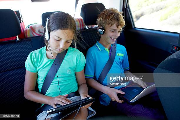 Boy and girl watching movies in back of car