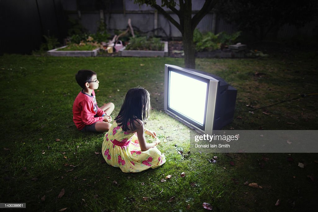 Boy and girl watching television : Stock Photo