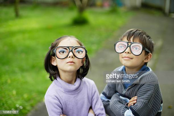 Boy and girl wear toy glasses