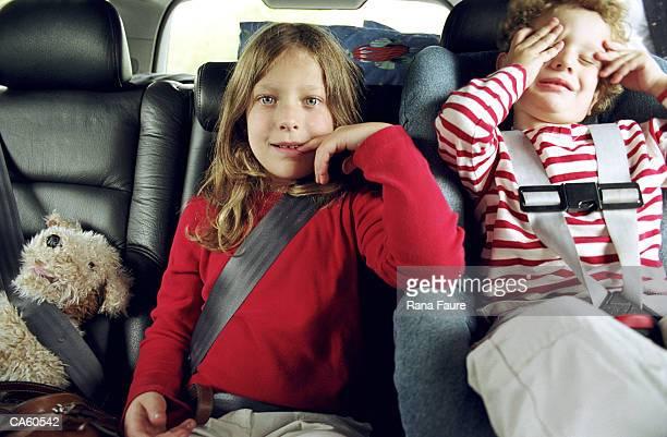 Boy and girl (2-4) wearing seatbelt in car