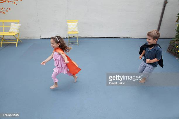 Boy and girl wearing superhero capes playing in back yard