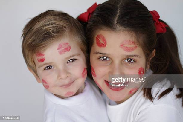 Boy and girl with lipstick kisses on their faces