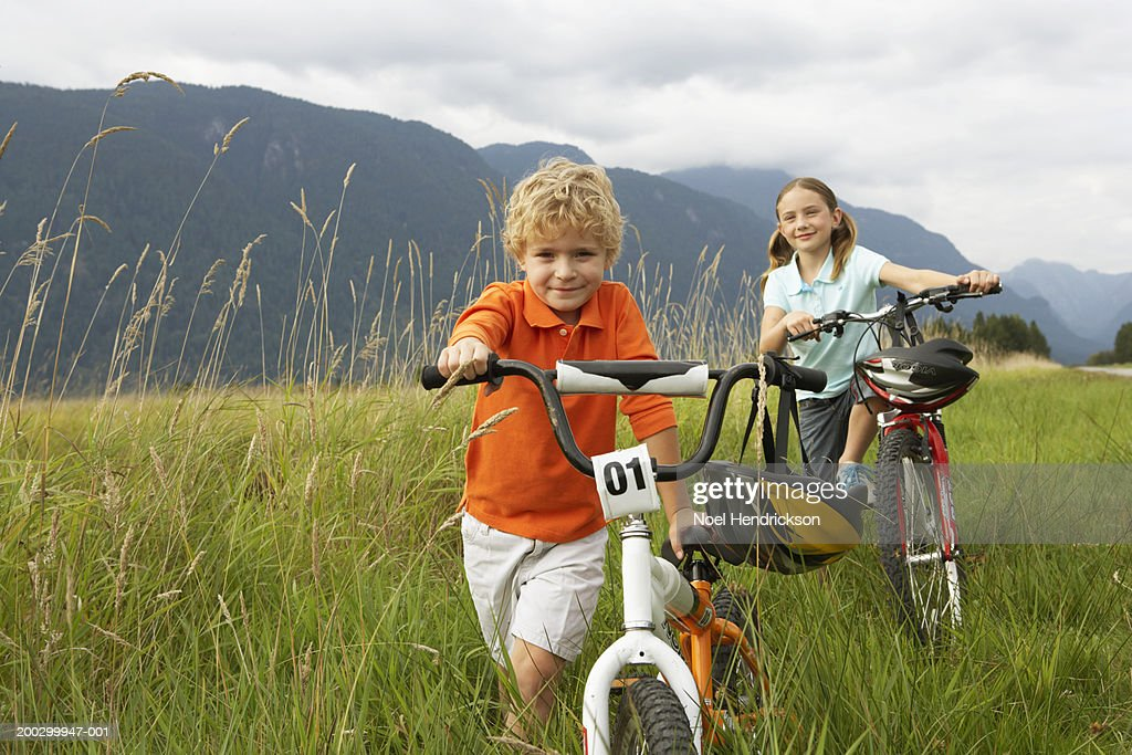 Boy and girl (5-8 years) with mountain bikes in long grass, smiling, portrait : Stock Photo