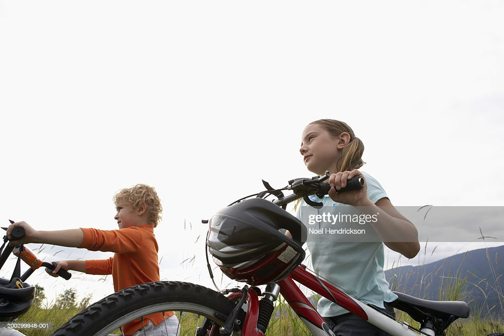Boy and girl (5-8 years) with mountain bikes, side view : Stock Photo