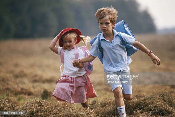 Boy (4-5) and girl (2-4) with satchel, running on grass