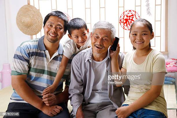 Boy and girl with their father and grandfather at home