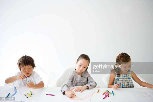 Boy and girls drawing picture side by side