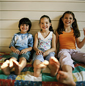 Boy and girls (5-9) sitting on porch, portrait