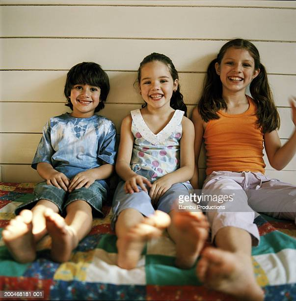 Boy and girls (5-9) sitting on porch, portrait