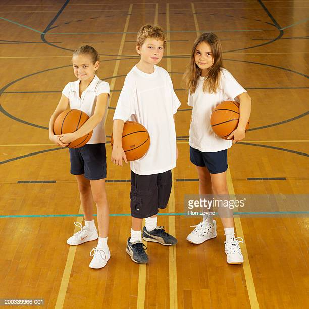 Boy and girls (8-11) with basketballs in gym, portrait