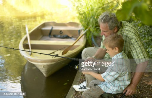 Boy (6-8) and grandfather fishing from side of lake : Stock Photo