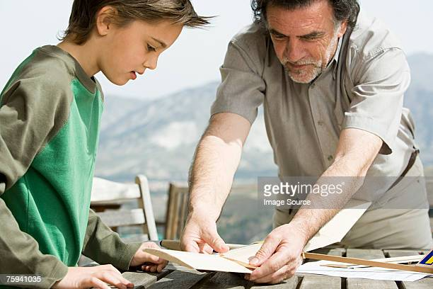 Boy and grandfather making toy aeroplane