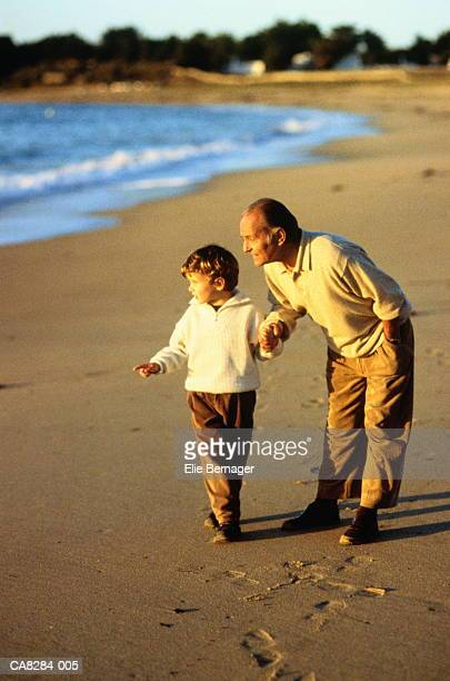 Boy (4-6) and grandfather on beach