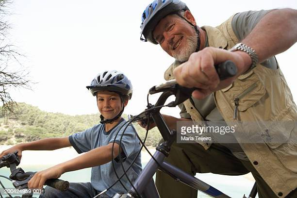 Boy (5-7) and grandfather on mountain bikes, smiling, portrait