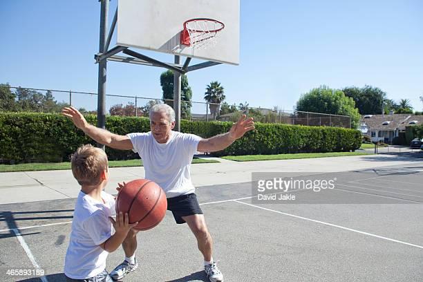 Boy and grandfather playing basketball