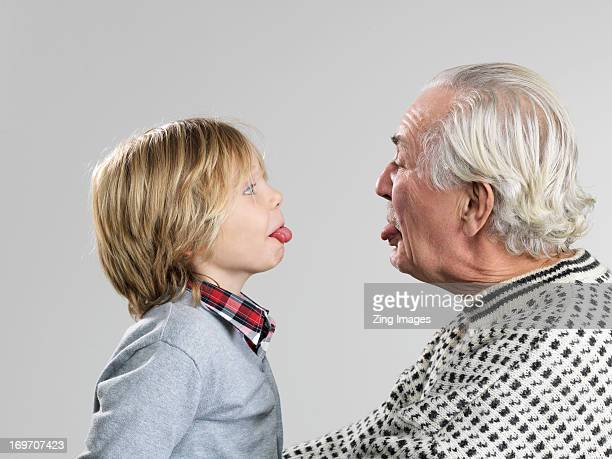 Boy and grandfather poking out tongues
