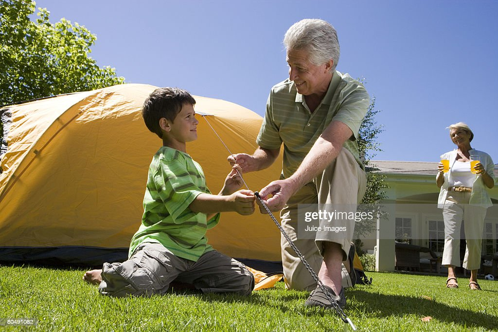 Boy (8-10) and grandfather tightening tent rope on garden lawn, grandmother serving orange juice in background, smiling (surface level) : Stock Photo