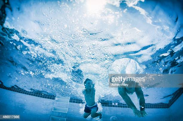 boy and grandpa diving into pool underwater