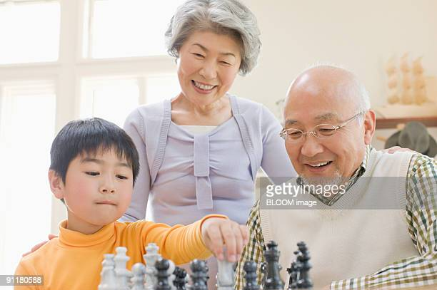 Boy and grandparents playing chess