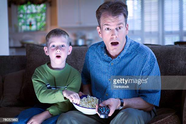 A boy and his dad look shocked at the television