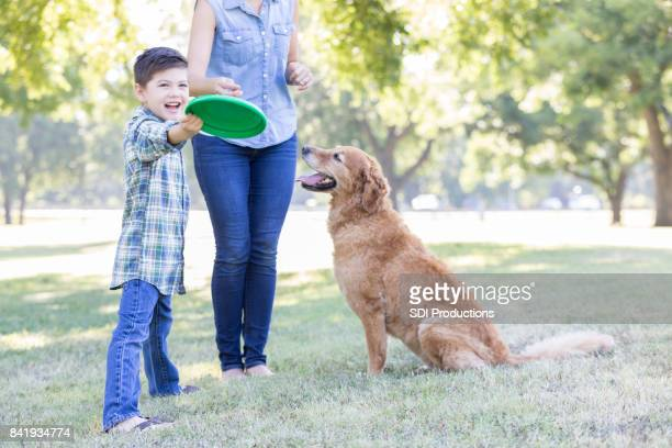 A boy and his dog play in the park together