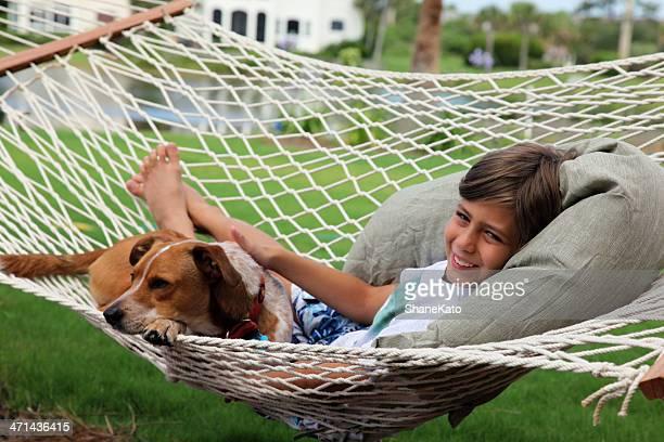 Junge und sein Hund beim Entspannen in der Hängematte
