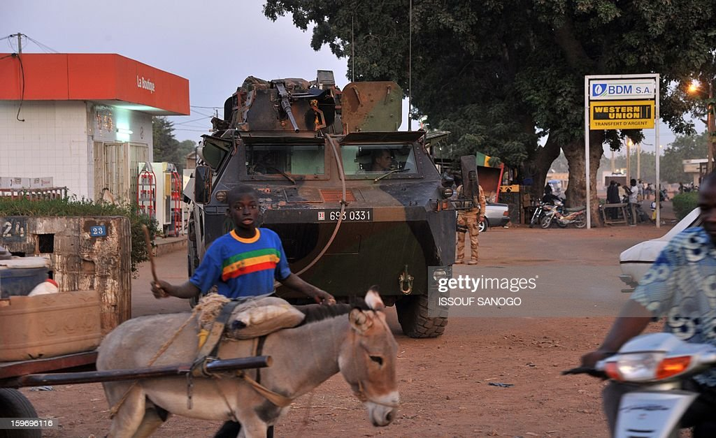 A boy and his donkey walk by French soldiers patroling in an armoured vehicle on January 18, 2013 in Markala. France confirmed today that Malian troops had taken control of the key central town of Konna from armed Islamists who seized the country's vast desert north in April last year AFP PHOTO / ISSOUF SANOGO