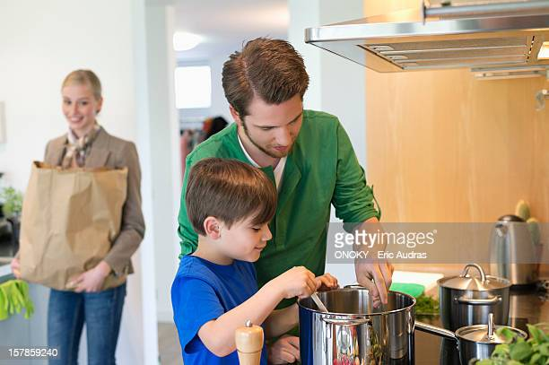 Boy and his father cooking in the kitchen while mother carrying a grocery bag