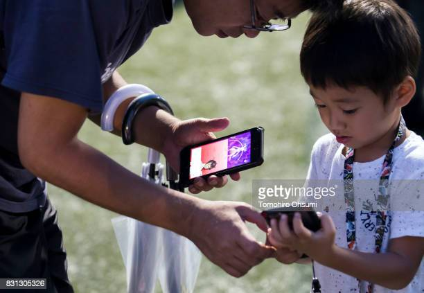 A boy and his father play Nintendo Co's Pokemon Go augmented reality game on their smartphones during the Pokemon Go Stadium event at Yokohama...