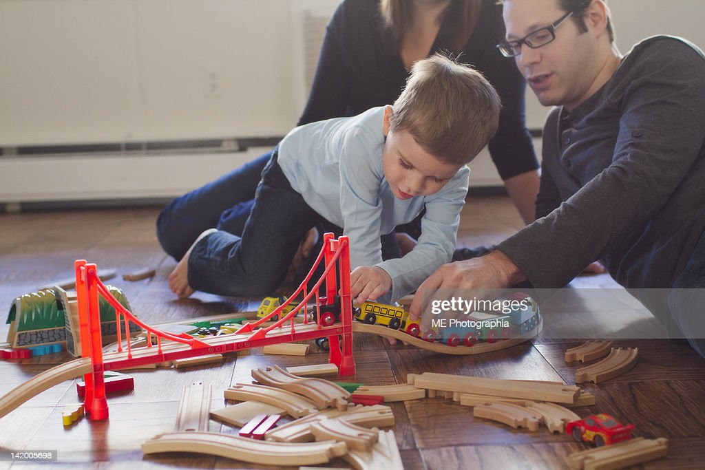 Boy and his father playing with wooden train