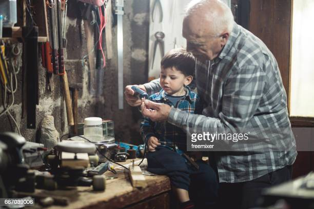 Boy and his gradpa in the workshop