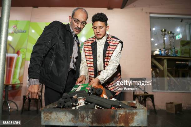 A boy and his Grandfather try to start a BBQ during a street festival in the southwestern suburb of Lakemba on May 27 2017 in Sydney Australia...