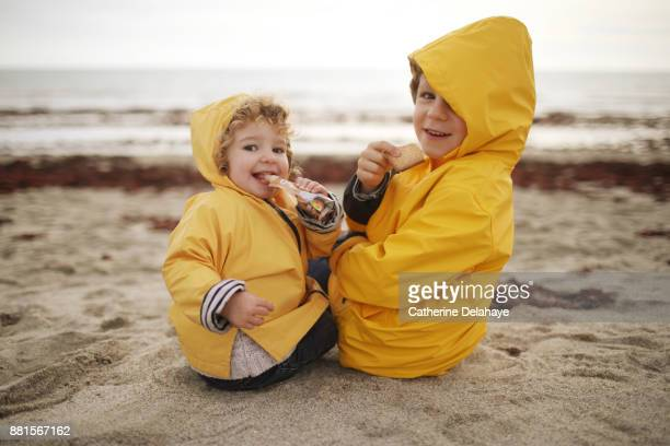 A boy and his little sister on the beach, they wear oilskins