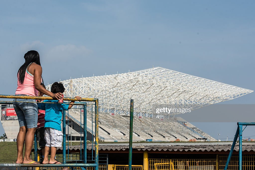 A boy and his mother play near the Itaquerao Stadium (Corinthians Arena) in Sao Paulo, Brazil on May 1, 2013. The stadium has been completed 70 % of the process and will host the opening match of FIFA World Cup 2014. AFP PHOTO/Yasuyoshi CHIBA