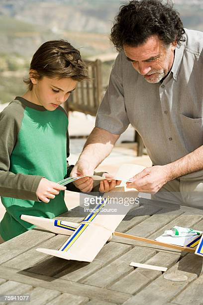 Boy and man making model aeroplane