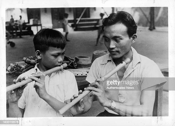 Boy and man playing wooden flute in Burma 1955