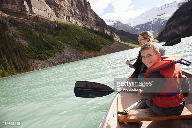 Boy and mom exploring lake with mountains in a canoe