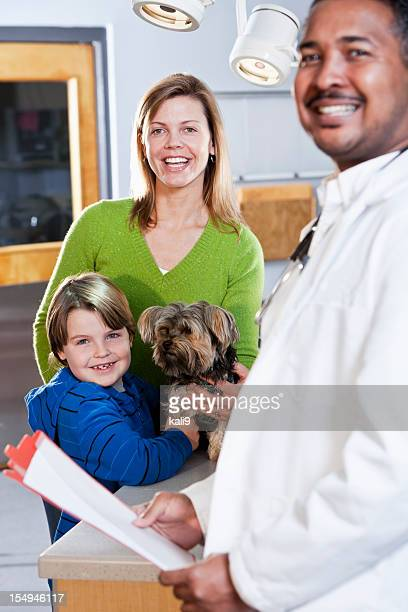 Boy and mother taking pet dog to vet