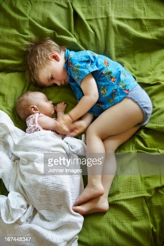 Boy and newborn baby on bed : Stock Photo