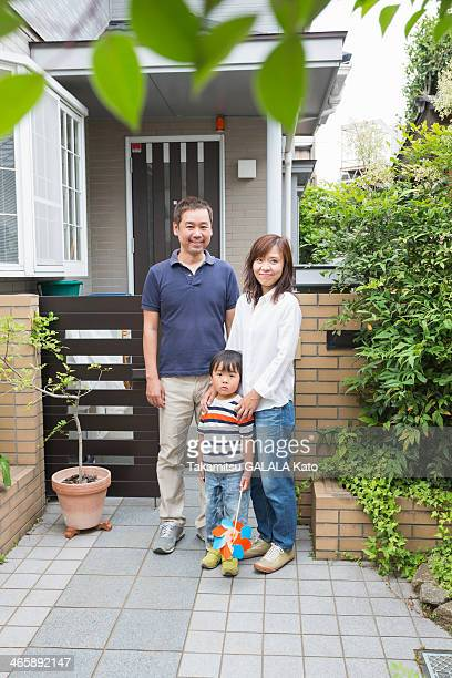 Boy and parents outside home